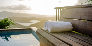 White towels rolled on a wooden bench overlooking the Caribbean Sea